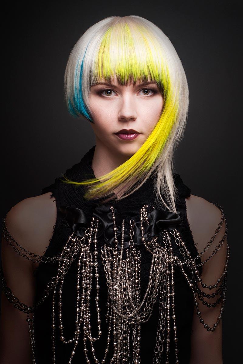 Asymetrický účes z polodlouhých vlasů.