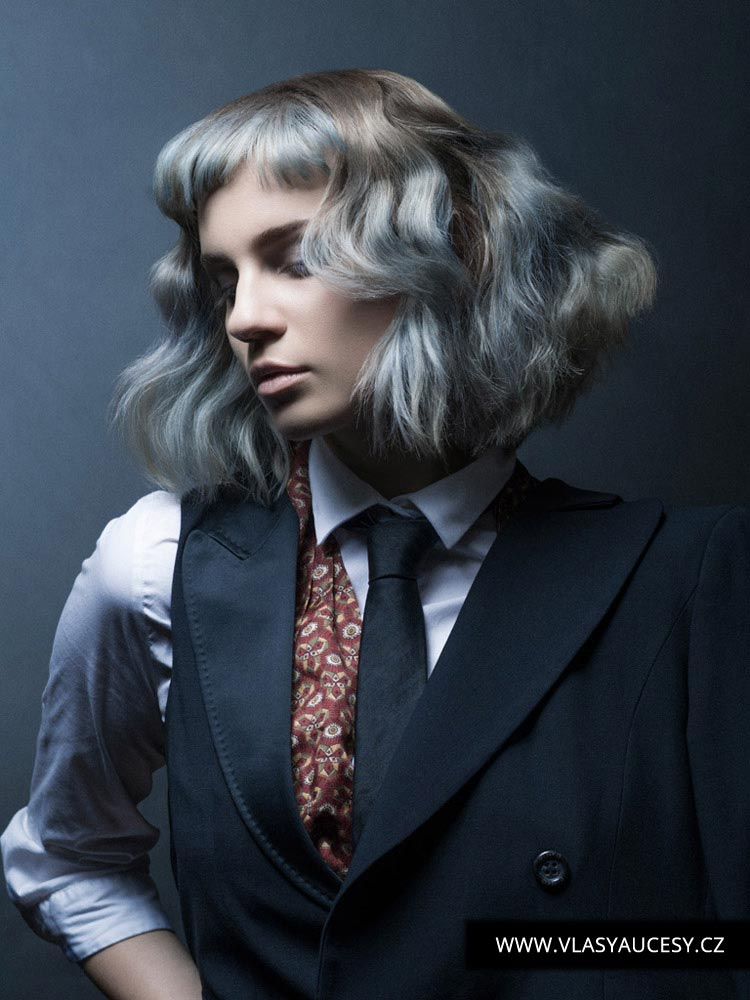 Polodlouhé vlasy brunetky i blondýny může oživit šedivý melír v kombinaci s modrými vlasy v barvě roku 2016 nazvané Serenity. Účes je z kolekce Kieran Tudor (BHA 2015).